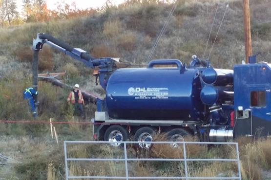 D&L Environmental Services septic truck pumping sludge & sewage at a job site.